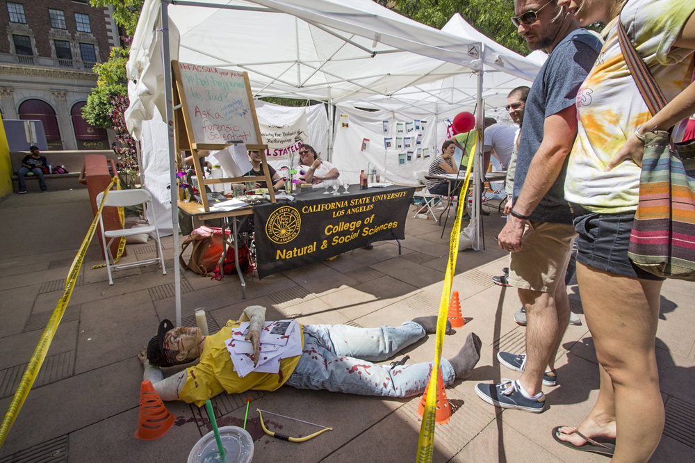 """Ask a forensic scientist!"" The March for Science in Downtown Los Angeles had several booths, like this one for CSUNs College of Natural & Social Sciences. They set up a crime scene to make it more interesting. April 22, 2017. (Jazz Shademan)"