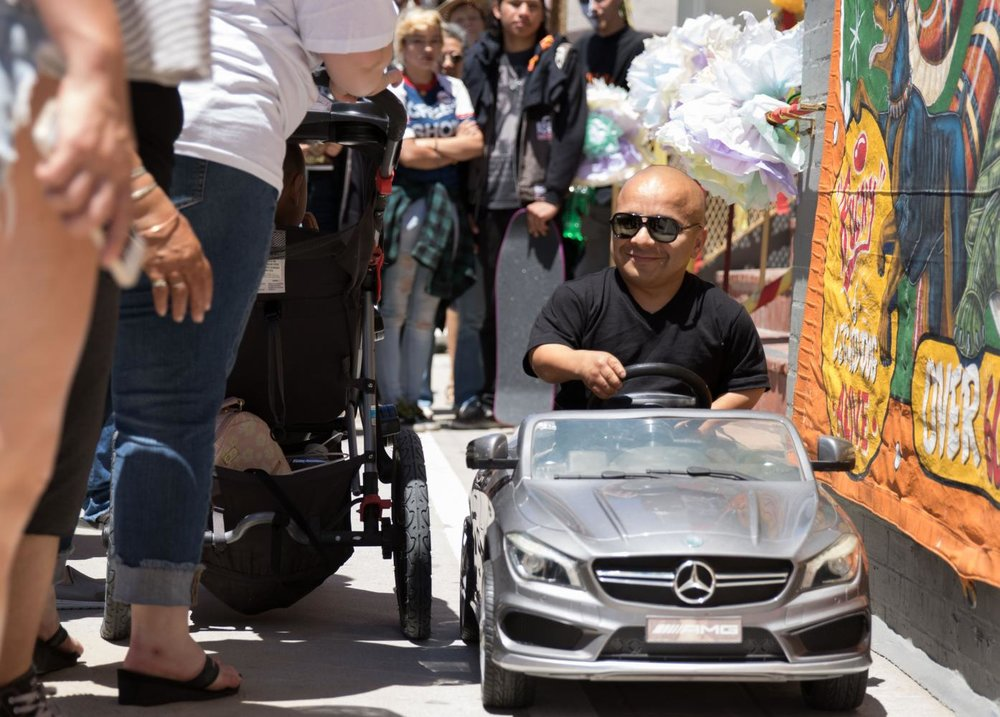 Venice Freakshow performer Gabriel, the smallest man in America takes his car for a ride around the boardwalk at the Venice Beach Freakshow Farewell Party and Protest in Venice California on April 30, 2017. Zane Meyer-Thornton.