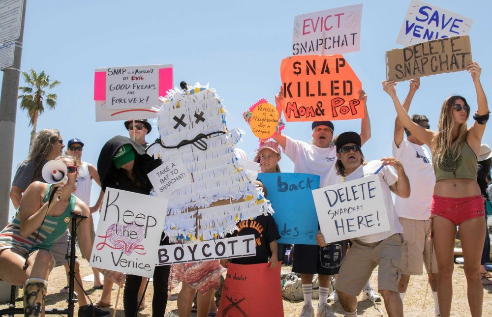 A group of protestors share Snapchats hidden agendas at the Venice Beach Freakshow Farewell Party and Protest in Venice California on April 30, 2017. Zane Meyer-Thornton.