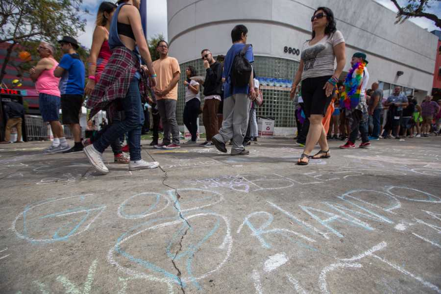 Los Angeles Gay Pride attendees walk through an area on Santa Monica Blvd. in West Hollywood that is being used to chalk messages of support for the victims of the shooting in Orlando, Florida. (Jose Lopez)