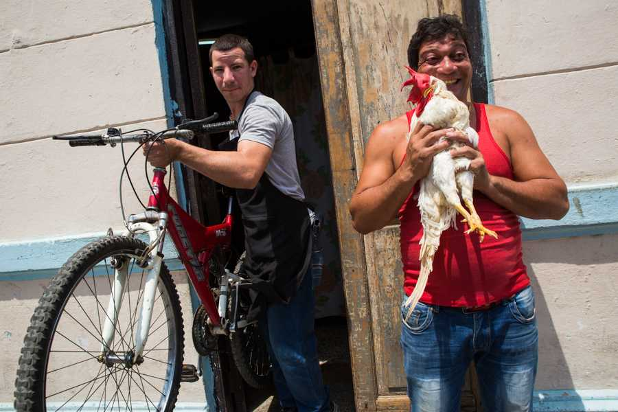 A man exits a building with his bike as another man picks up and holds his pet rooster joyfully. Jose Lopez