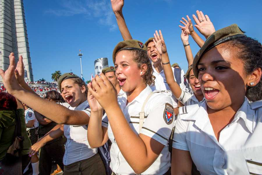 Young school girls filled with energy cheer patriotically as they participate in the May Day march in front of the José Martí Memorial Monument at the Plaza de la Revolución in Havana, Cuba on May 1, 2016. Hundreds of thousands of people participated in this years May Day celebration that exhibited a strong patriotism and joyful commitment by Cuban citizens to their country as they carried banners and signs with images of revolutionary heroes and messages. Jose Lopez