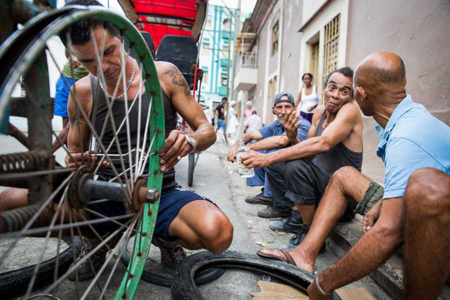 A Cuban man repairs the spokes on his pedicab bicycle while friends socialize on the sidewalk in Havana, Cuba on May 2, 2016. In 1962 President John F.Kennedy officialized the embargo against Cuba which has inspired a local culture of ingenuity where repairing anything and everyting has become the solution when replacing is not an option. (Jose Lopez)