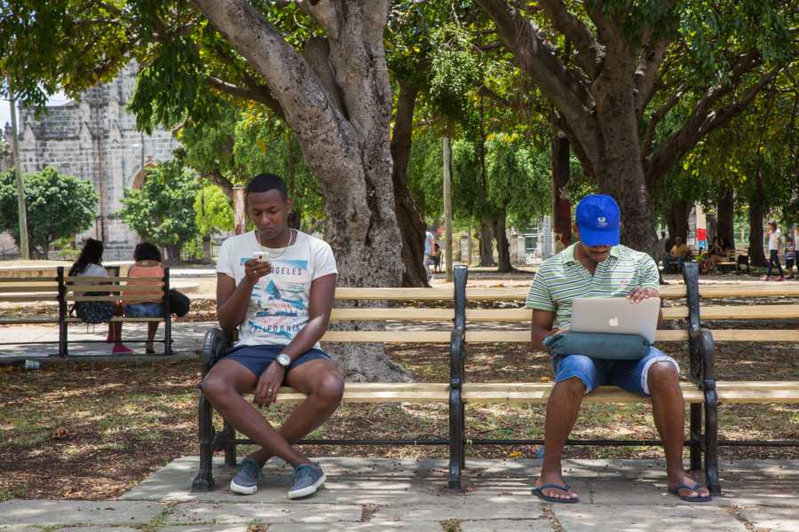 "Cubans gather at the ""15 y 18"" park in the Vedado neighborhood of Havana to take advantage of a public Wi-Fi hotspot signal that allows them to get online with their phones and laptops. Available for almost 2 years, Wi-Fi internet access is relatively new on the island at a cost of $4.50 to foreigners and $2 to Cubans per hour. Wi-Fi access has become so popular that you can find crowds gathering all day and night around hotspots situated near parks, hotels, and other locations. Jose Lopez"