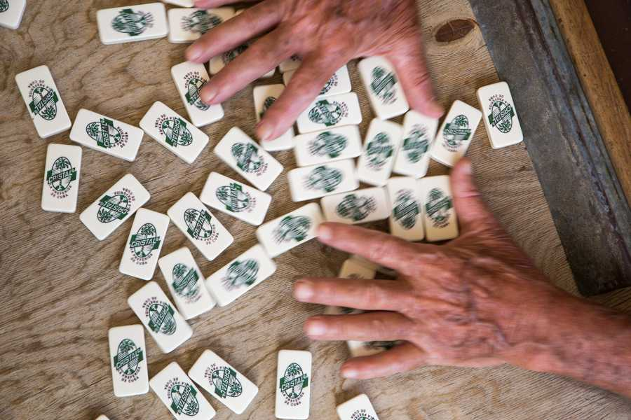 A man shuffles dominoes before beginning a game at a community space in Havana, Cuba. Jose Lopez