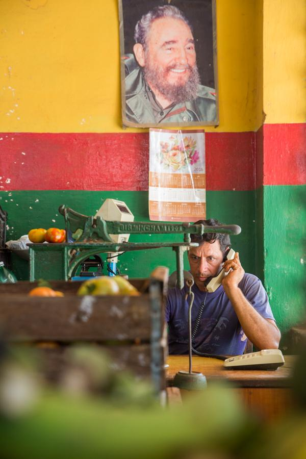 A man steps away from his work of sorting fruit in a small produce market to answer the phone where hanging above him is a portrait of Fidel Castro. Jose Lopez