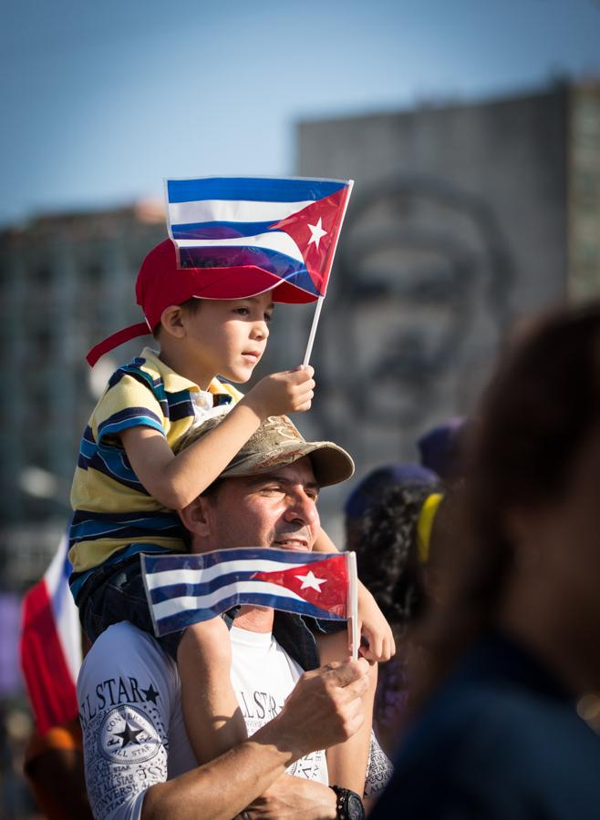 A man marches with his child on his shoulders in front of the Ministry of Interior building in Plaza de la Revolución during May Day in Havana, Cuba on May 5, 2016. Starting at 4am the streets began to fill with people til they were packed for miles with people celebrating the day with patriotic fervor. (Jose Lopez)