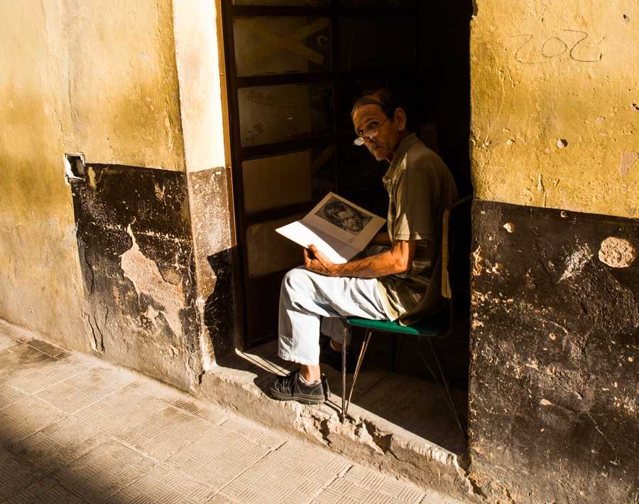 A man looks up from his reading in the shade as the bright sun shines in Havana, Cuba. Jose Lopez