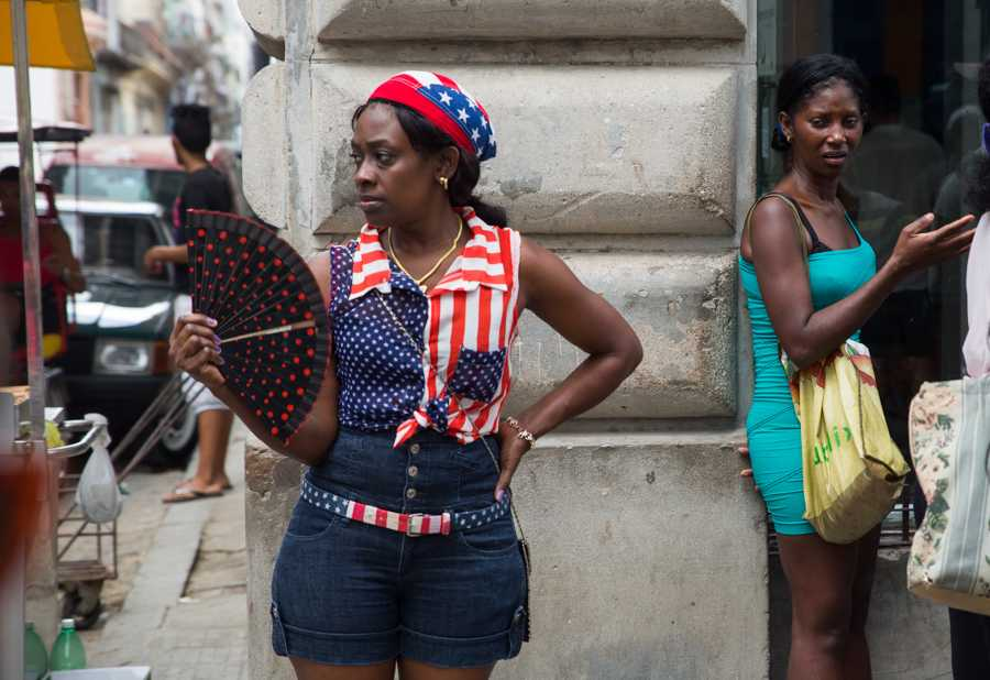 A woman gathers along a street in Old Havana while being dressed in a fashion that represents the United States flag. The U.S. flag is interestingly popular in Havana and can be found in many forms which include fashion, on pedicabs, and on air fresheners in cars to name a few. Many Cubans share that their issue is not with the American people but rather with the embargo and American policy that unjustly limits the opportunities of people on the island. Jose Lopez