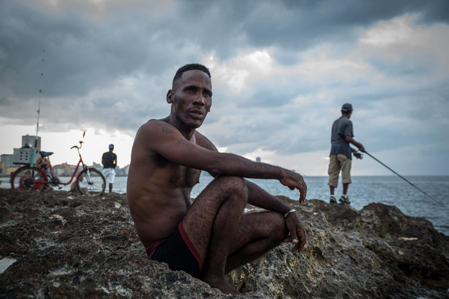 A man sits on the rocks at the malecon seawall area enjoyng the ocean view along with fishermen and divers in Havana, Cuba on May 3, 2016. The malecon is a popular social destination for many Cubans who may have plenty of time to spend but little money. In the day its a place for bathing, while at night the sidewalk along the malecon will become active all night long transforming into social hotspot alternative to clubs. (Jose Lopez)