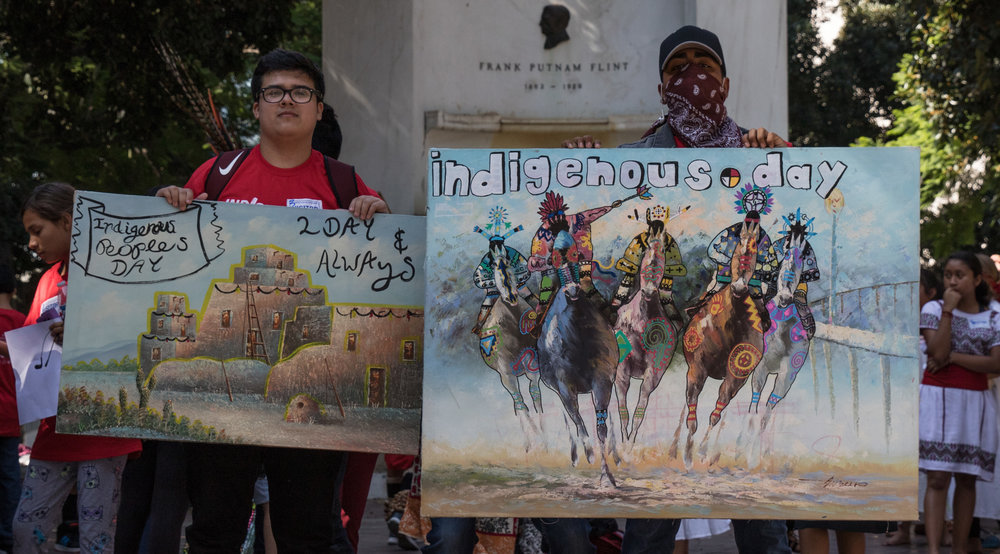 Jaime Arguelles (left) and Isaac Ramirez (right) show off their signs in support of Indigenous Peoples Day replacing Columbus Day on August 30, 2017 at Los Angeles City Hall in Los Angeles California (Photo By: Zane Meyer-Thornton)