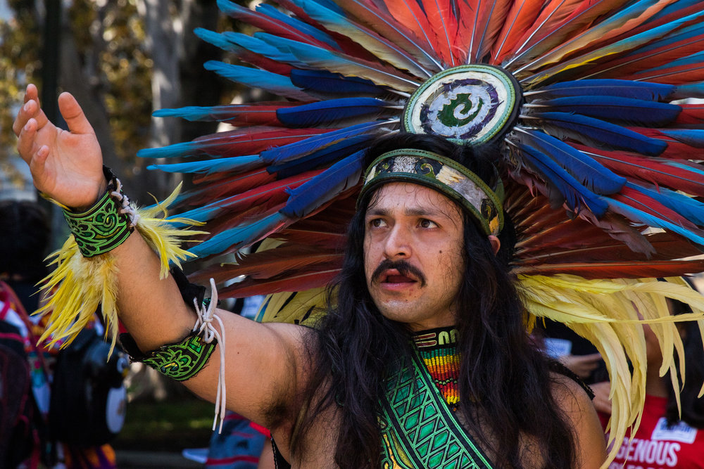 Xochipilli guides his students towards the outside of Los Angeles City Hall due to an overflow of people in the building. This was part of a successful attempt to replace Columbus Day with Indigenous Peoples Day in Los Angeles, California on August 30, 2017. (Photo By: Zane Meyer-Thornton)