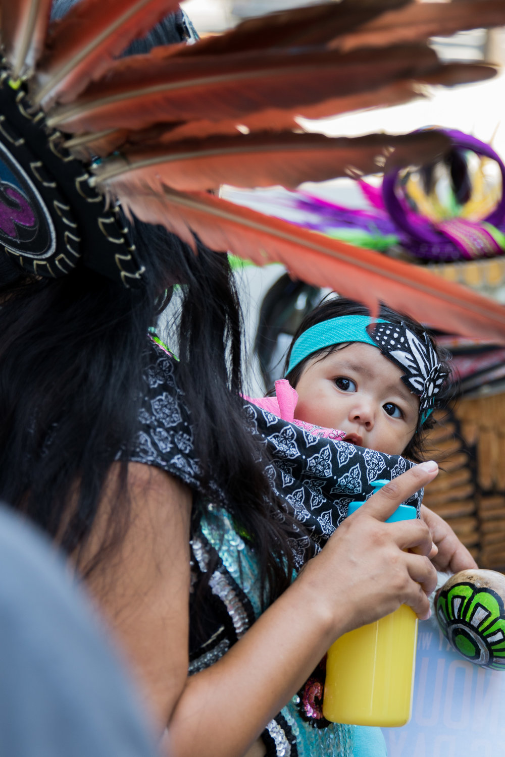 Lilia Herrera (left) takes a break to feed her daughter Xochipilli Herrera (right) at Los Angeles City Hall for the replacement of Columbus Day with Indigenous Peoples Day which was successful on August 30, 2017 in Los Angeles, California (Photo By: Zane Meyer-Thornton)
