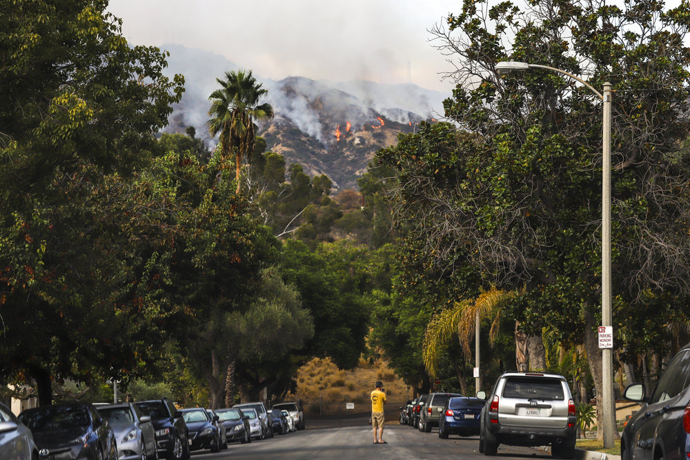 La Tuna Fire continues to burn through the Labor Day weekend in Burbank, Ca on September 2, 2017. A man comes out of his home to take snap a photo near intersections of Magnola and Sunset Canyon. The wildfire started due to the ongoing heatwave in Los Angeles. (Jazz Shademan)