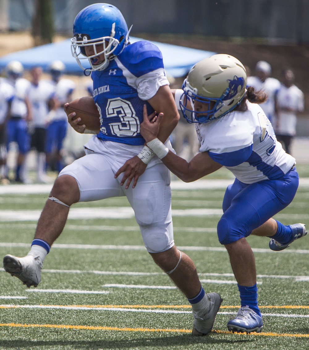 The Santa Monica College Corsairs Mens football Team player runningback Kahlil Miller (23) (blue,left) runs in for a touchdown passing The West La College Wildcats defensive back Alexander Leota (white,right) (37), Friday, September 2nd, 2017, at West La College in Culver City, CA. The Corsairs beat The Wildcats 31-30. (Daniel Bowyer/Crsair Staff)