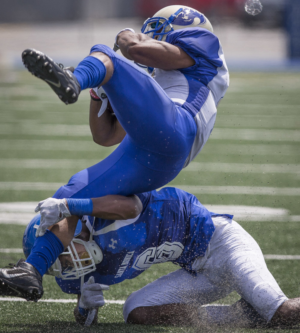 The Santa Monica College Corsairs Mens football Team defensive back Tyree Fryer (23) (blue,bottom) makes a tackle against The West La College Wildcats running back Drexel Mosby (white,top) (11), Friday, September 2nd, 2017, at West La College in Culver City, CA. The Corsairs beat The Wildcats 31-30. (Daniel Bowyer/Crsair Staff)