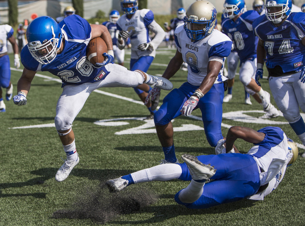 The Santa Monica College Corsairs Mens football Team player wide reciever Terrence Jones II (26) (blue,left) fights for yards after a complted pass against The West La College Wildcats, September 2nd, 2017, at West La College in Culver City, CA. The Corsairs beat The Wildcats 31-30. (Daniel Bowyer/Crsair Staff)