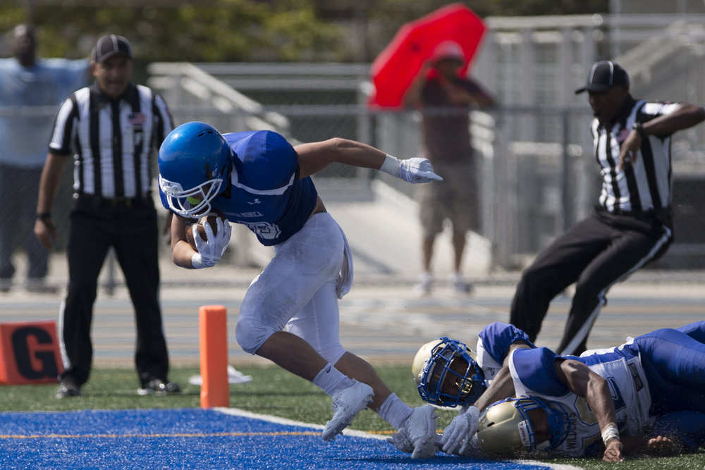 Santa Monica Corsair Christoph Hirota (5)(left) breaks a tackle from West Los Angeles Wildcats Aaron Brown (7)(center) and Alexander Johnson (42)(right) to score a touchdown during the third quarter on September 2, 2017 at West Los Angeles College in Culver City, California. The Corsairs win their first game against the Wildcats 31-30. (Jose Lopez)