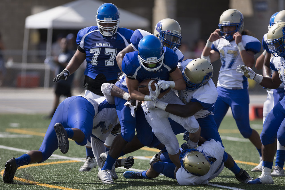 Santa Monica Corsair Christoph Hirota (RB)(5) gets tackled by the West Los Angeles Wildcats on September 2, 2017 at West Los Angeles College in Culver City, California. The Corsairs win their first game against the Wildcats 31-30. (Jose Lopez)