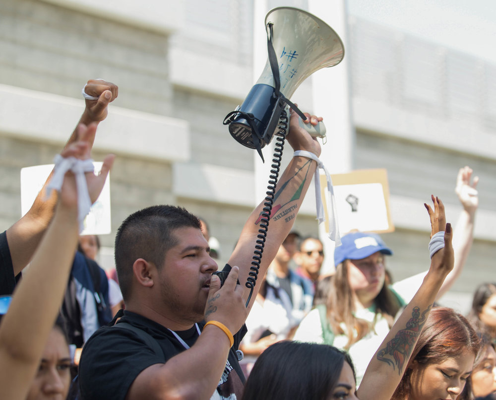 "Edgar Gonzalez raises his Megaphone in the air along with other protesters raising their arms to show the strength they have to fight for DACA and against discrimination. The students chant phrases like ""No papers, no fear"" and ""Undocumented, unafraid"" in front of Santa Monica College's library on main campus, Santa Monica, Calif. (Photo by: Thane Fernandes)"