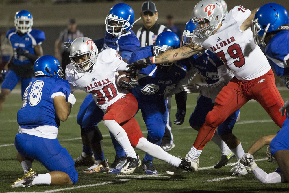 Palomar College Comet Edwin Morton (RB)(30)(left) struggles to break free from a tackle by the Santa Monica College Corsairs on September 10, 2017 on the Corsair Field at Santa Monica College in Santa Monica, California. The Corsairs lose to the Comets 14-45. (Jose Lopez)
