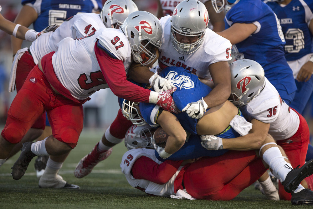 Santa Monica College Corsair Christoph Hirota (RB)(5)(center) gets tackled by the Palomar College Comets on September 10, 2017 on the Corsair Field at Santa Monica College in Santa Monica, California. The Corsairs lose to the Comets 14-45. (Jose Lopez)
