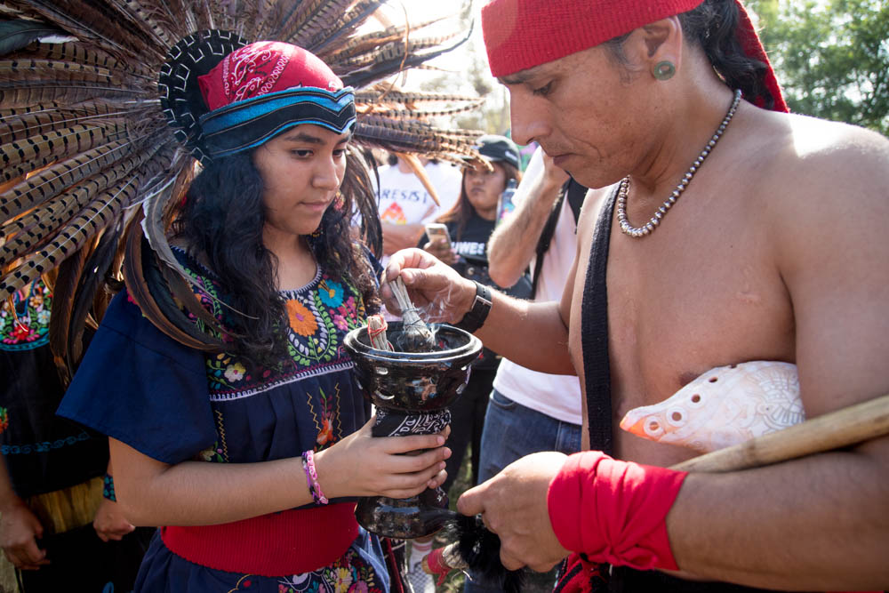 Krystal Nicole Escalante and Marcos Aguilar, director of Anahuacalmecac International University Preparatory, light the bowl of sage. It's all part of their ceremony before the Defend Daca March takes place on September 10, 2017 in Macarthur Park, Los Angeles CA. (Jazz Shademan)