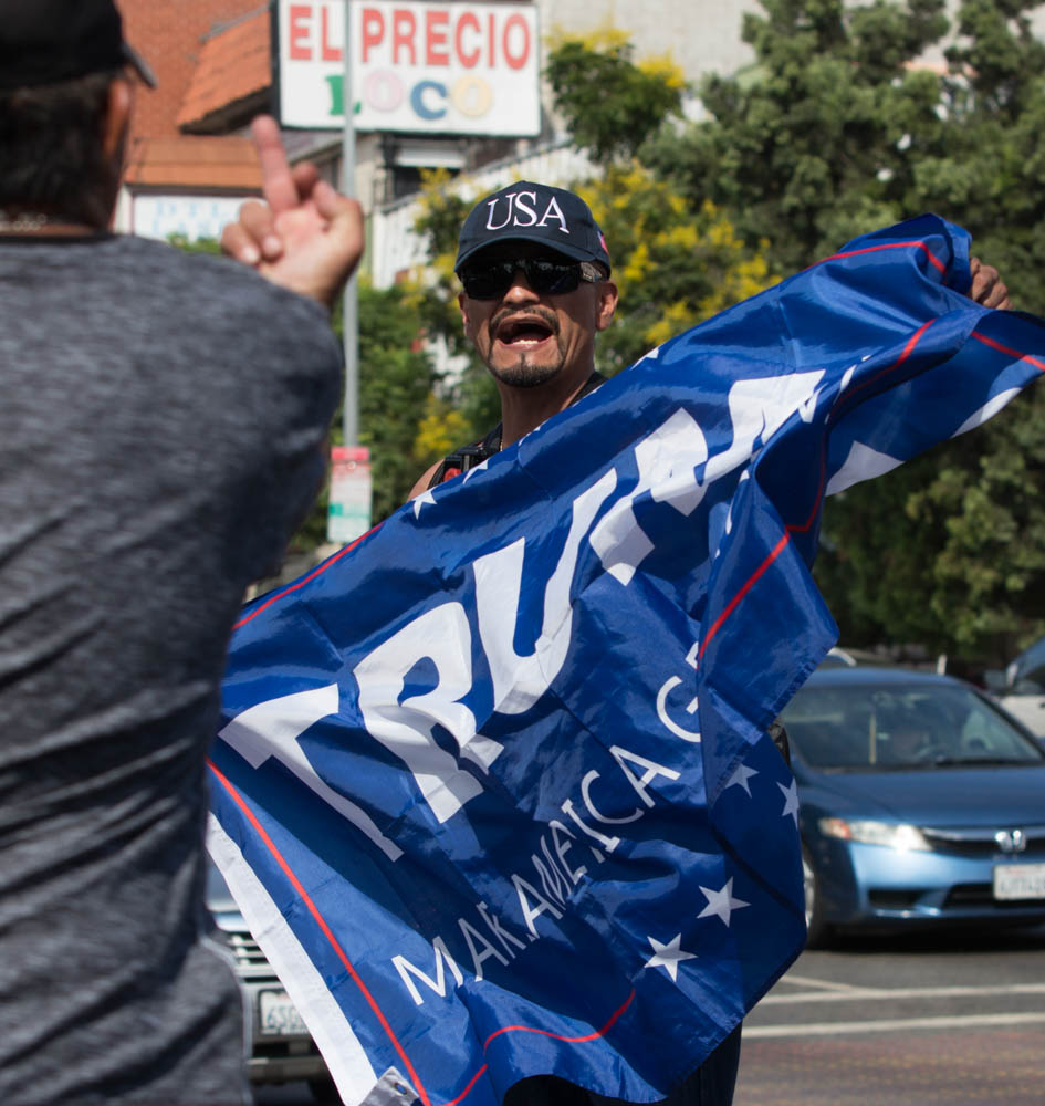 A DACA supporter argues with an anti-immigrant protester waving a Trump flag as the pro-DACA march begins to move down 6th street near MacArthur Park in Los Angeles, California on September 10, 2017. (Jose Lopez)