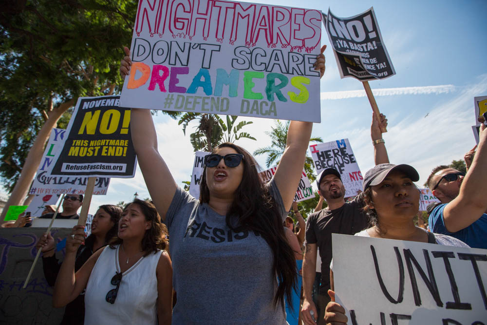 Pro-Daca supporters gathering for a march to Olvera Street hold up their signs in defiance of a small group of anti-immigrant protesters who have gathered on the other side of 6th street from MacArthur Park in Los Angeles, California on September 10, 2017. (Jose Lopez)