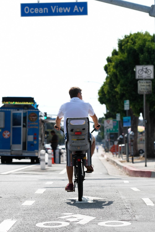 A man rides across Ocean View Av on the new bike lane that runs down Venice BLVD in Los Angeles, CALIF on September 19th, 2017.(Photo by Jayrol San Jose)