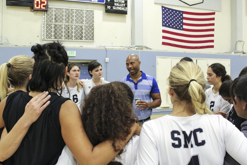 SMC Head Coach, Turhan Douglas, (middle) huddles with the women's volleyball team during a break in the action from their thrilling 3-1 set victory against the Marauders of Antelope Valley in the Corsair Gymnasium, located on the Santa Monica College Main Campus, in Santa Monica, Calif, on Wednesday, September 27th.  (Photo by Ivanna Gamboa/Contributor)