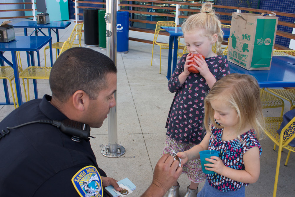 Officer Gustavo Cortez (left) gives two year old Sienna Robertson (right) a Police Helper sticker during National Coffee with a Cop Day held at Groundwork on Wednesday, October 4, 2017, in Santa Monica, Calif. This event began in 2011 to help promote the community and officer to sit down and talk to bring them together.(Photo by: Brian Quiroz)