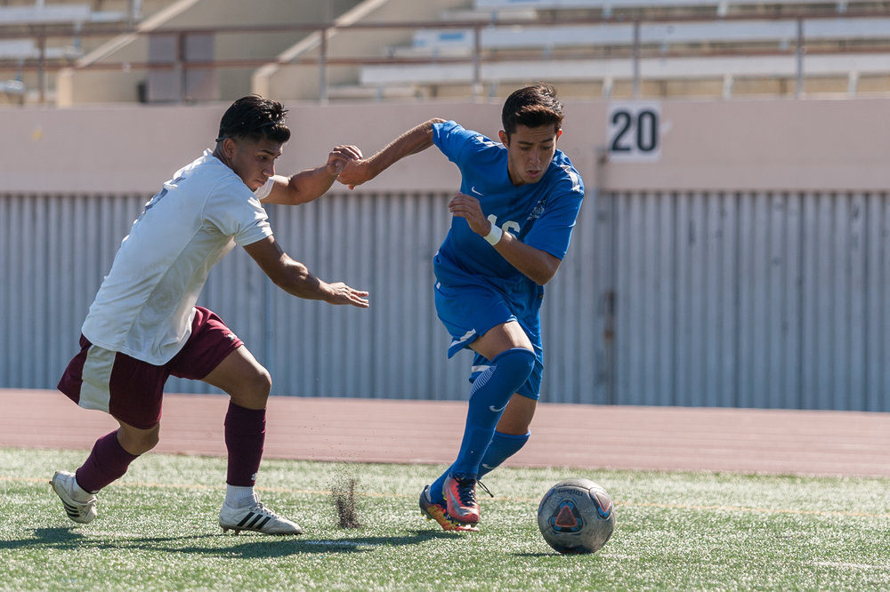 Midfielder Carlos Rincon (16,right) moves the ball up the field while being contested by Angel Barajas (5,left) of Victor Valley College. The Santa Monica College Corsairs won the game 2-0 against the Victor Valley Rams. The match was held at the Corsair Stadium at Santa Monica College in Santa Monica, Calif. on October 6, 2017. (Photo by: Justin Han/Corsair Staff)