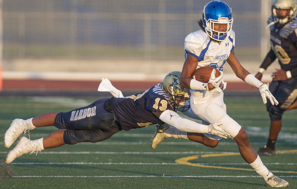 The Santa Monica College Corsairs Mens football Team player wide reciever Eric Bet (83) (white,right) beats a tackle by The LA Harbor College Seahawks saftey Logoleo Tulafano (blue,left) (13), Saturday, September 30th, 2017, at LA Harbor College in San Pedro, CA. The Corsairs loose to the Seahawks 28-21. (Daniel Bowyer/Corsair Staff)