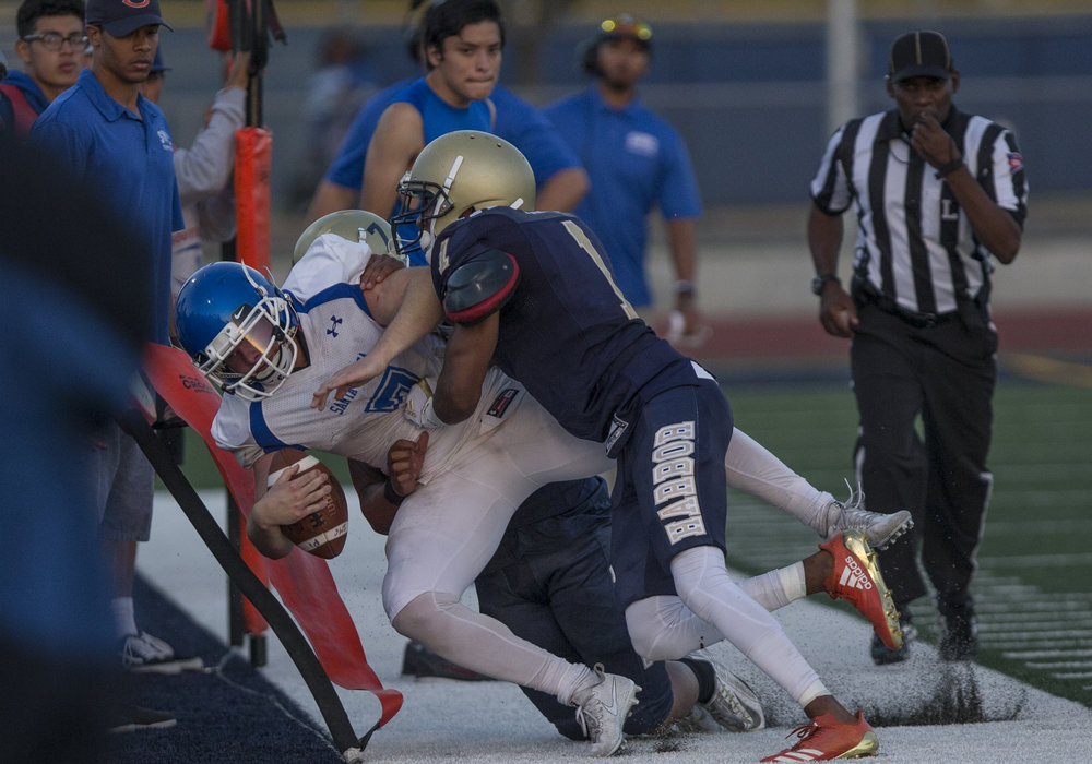 The Santa Monica College Corsairs Mens football quarterback Nick Hutchins (7) (white,left) gets tackled out of bounds by The LA Harbor College Seahawks, Saturday, September 30th, 2017, at LA Harbor College in San Pedro, CA. The Corsairs loose to the Seahawks 28-21. (Daniel Bowyer/Corsair Staff)