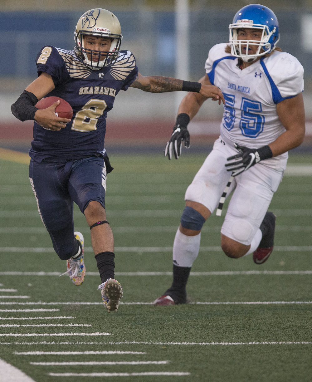The Santa Monica College Corsairs Mens football defensive lineman Luta Mailoto (55) (white,right) runs The LA Harbor College Seahawks quarterback Demetrius Reed (2) (blue,left) out of bounds, Saturday, September 30th, 2017, at LA Harbor College in San Pedro, CA. The Corsairs loose to the Seahawks 28-21. (Daniel Bowyer/Corsair Staff)