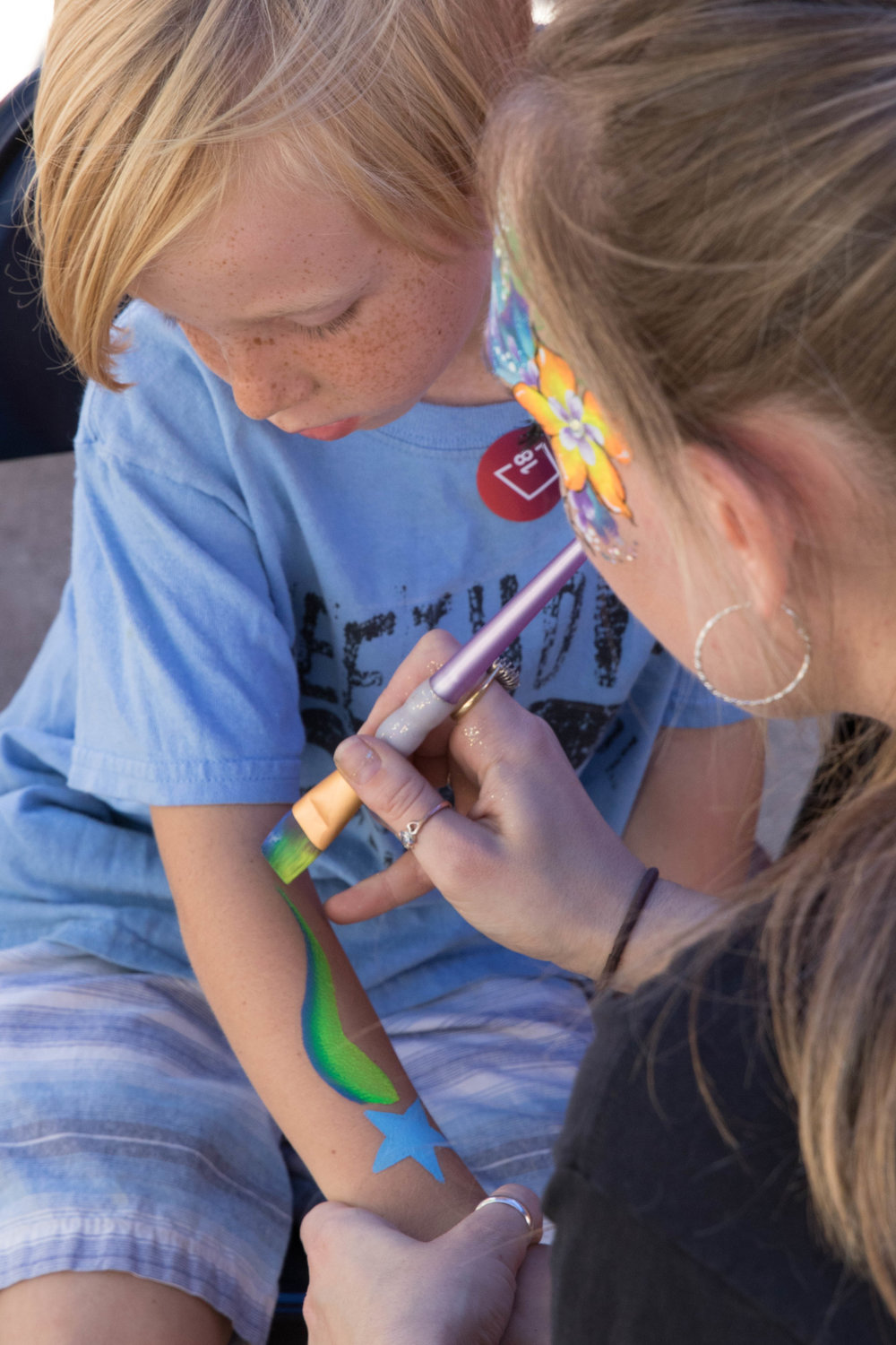 Rylan Boothby (left) gets an arm drawing done by Oriana as part of the Pico Block Party on October 14, 2017 (Photo By: Zane Meyer-Thornton)