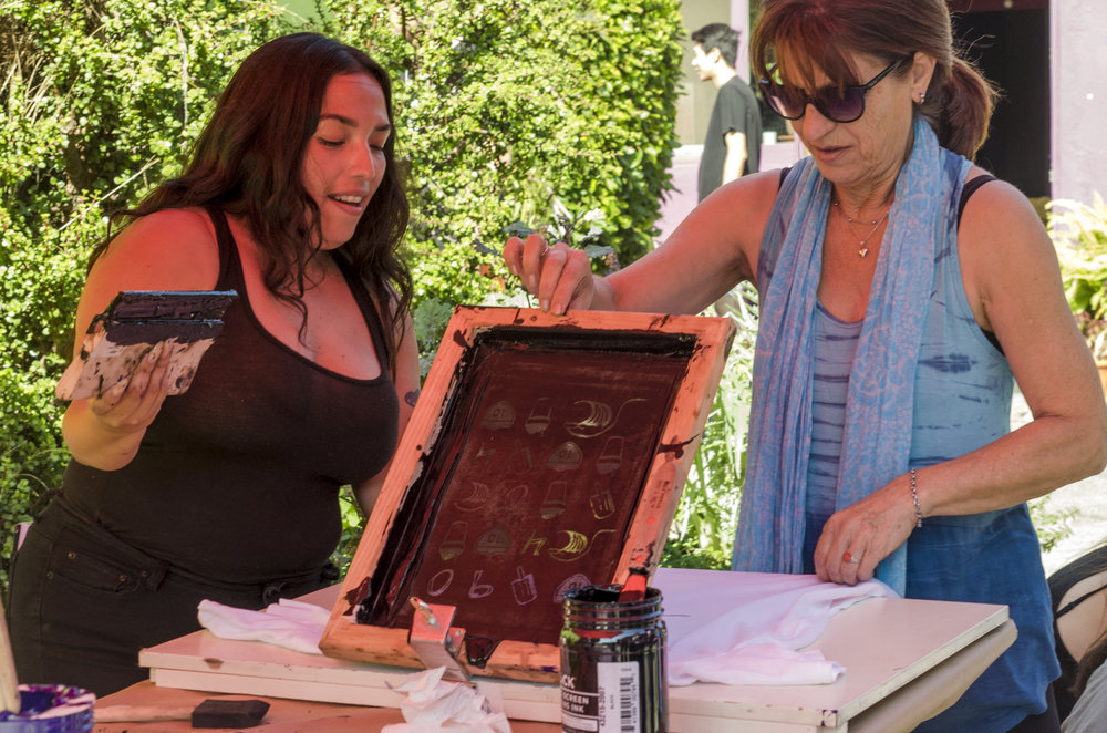 Free T-shirts to screen print were done at the Pico Block Party. Christina Saucedo (left) showing a participant of the Pico Block Party how to screen print. 18th Street Art Center on 18th and Olympic. Santa Monica, Calif. October 14, 2017. (Photo by Diana Parra Garcia)