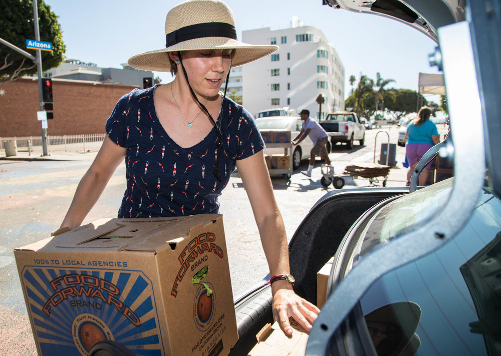 Director of Student Assistance at Santa Monica College, Ana Laura Paiva, helps load a trunk full of boxes carrying produce. The boxes are collected from participating farmers in the Food Forward program. On October 25, 2017 over thirty boxes were collected at the Santa Monica Farmers Market in Santa Monica, Calif. The boxes are then transported to Santa Monica College for the Free Corsair Farmers Market located in the Organic Learning Center. (Photo: Jazz Shademan)