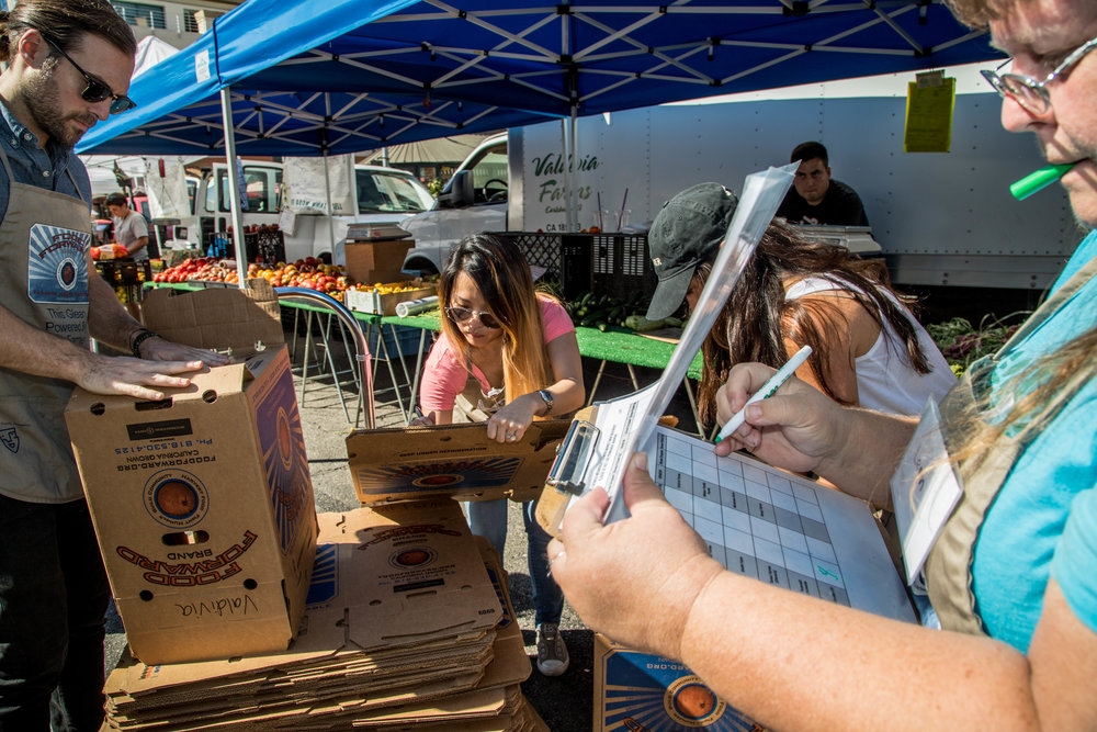 The group of volunteers that help collect, organize, and keep track of how many boxes are being donated from each vendor are called the Glean Team from Food Forward. On October 25, 2017 they start their run nearing the end of the Farmers Market in Santa Monica, Calif.  Eric Barber (L), first-time volunteer, prepares folding boxes to give out to participating vendors as Leann Bogart (R), SMC student and Food Forward volunteer keeps count. (Photo: Jazz Shademan)