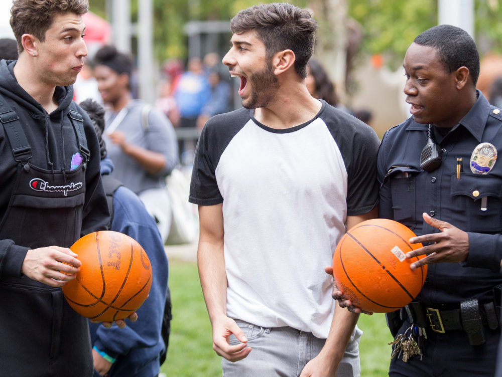 Cousins Marcus Nasrollahy (CQ left) and Eman Vafa (middle) shoot hoops with Santa Monica College Police Officer Jester (right) on the Santa Monica College's Main Campus Quad for the Associated Students' Homecoming Carnival on Halloween on Tuesday, October 31st 2017 (Photo by: Thane Fernandes)
