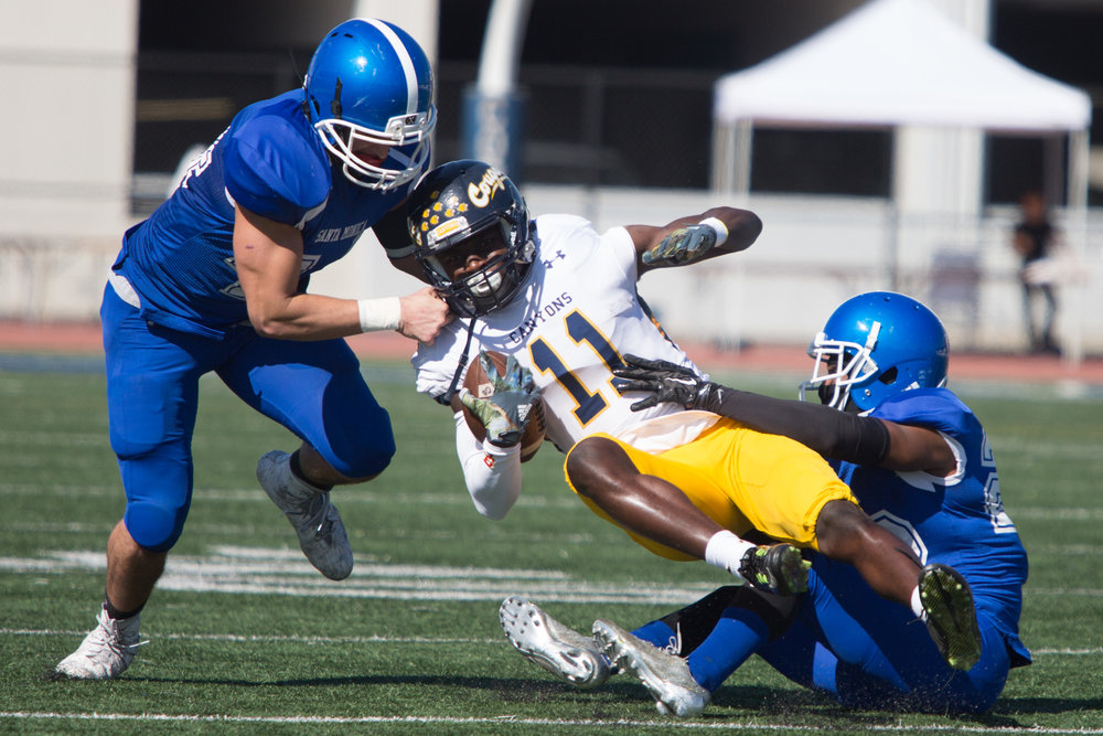 Linebacker Chris Wein (44, Left) and Defensive back Richard Harbor III (22, Right) of Santa Monica College Corsairs attempt to tackle Wide receiver Jarrin Pierce (11,Middle) of College of the Canyons Cougars during 2nd quarter of their homecoming game. On Saturday, November 4th, 2017 at Corsair Stadium in Santa Monica College Main Campus in Santa Monica, California. (Photo by Yuki Iwamura)