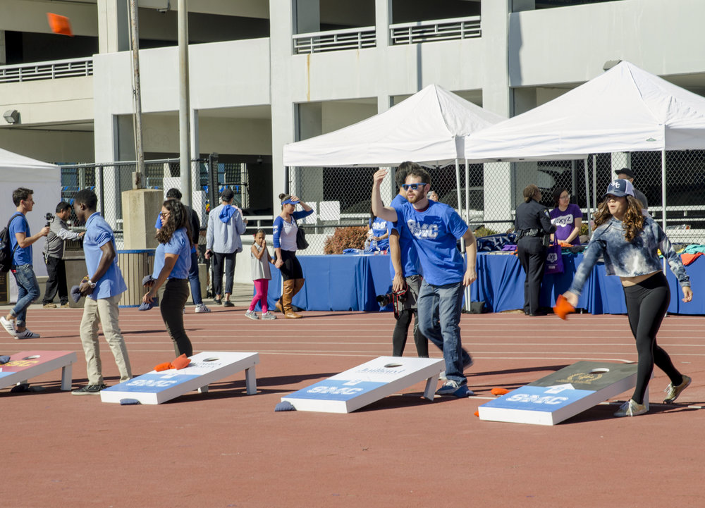 Santa Monica College students and alumni playing bean bag toss with each section showing the transfer school that SMC transfers to. Santa Monica College football field in Santa Monica,Calif. November 4, 2017. (Photo by: Diana Parra Garcia)