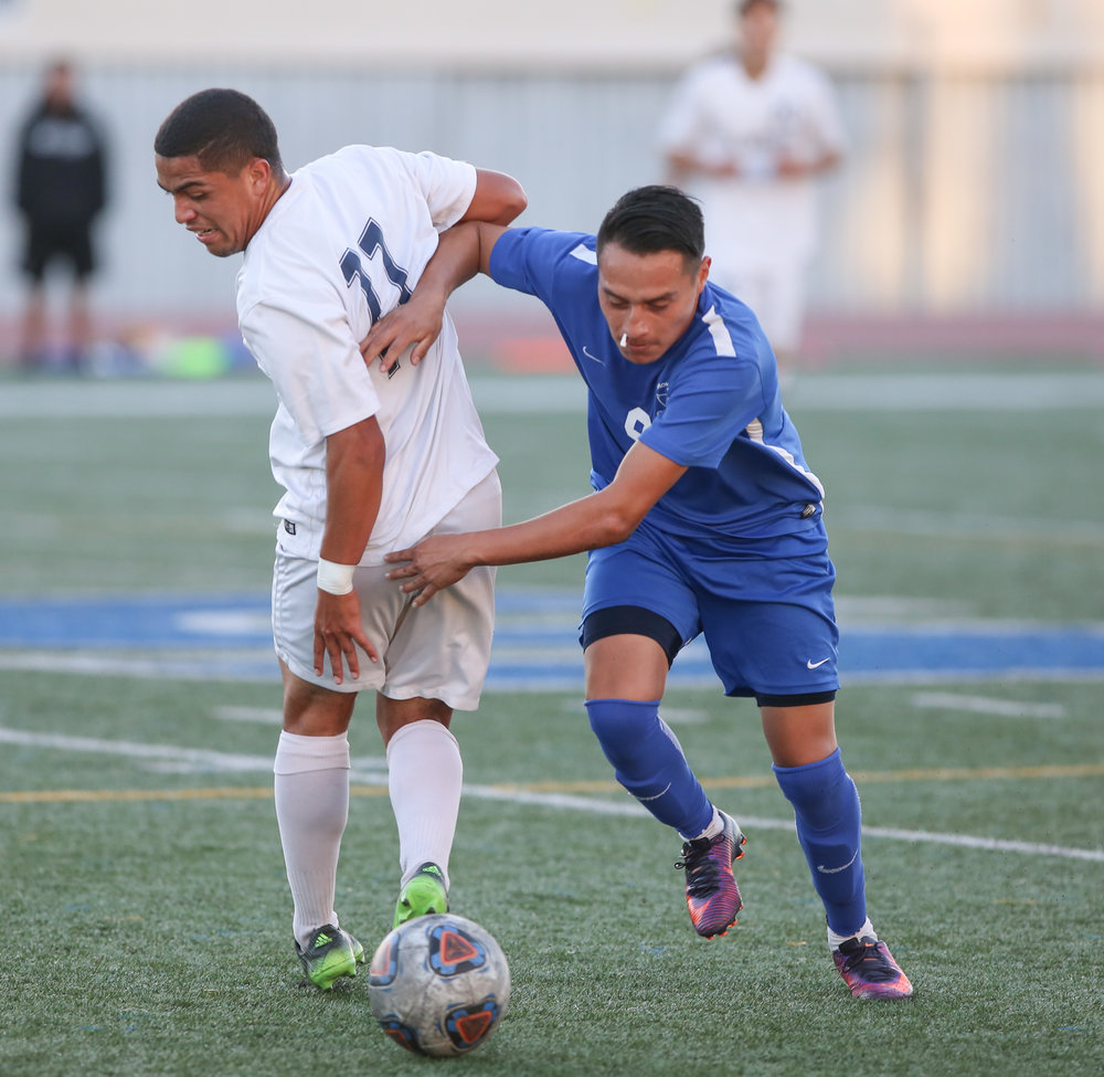Chris Negrete (9 right) runs around Javier Moran (11 left) to get the ball during the soccer game between Santa Monica College's Corsairs and L.A. Mission College's Eagles at the Corsair Stadium at Santa Monica College in Santa Monica, Calif on Tuesday, Nov 7th 2017. Earlier in the game, Chris got a bloody nose after bumping into another player and had cotton in his nose to prevent further bleeding. The game ended in a win for the Corsairs with a final score of 2-1. (Photo by: Thane Fernandes)