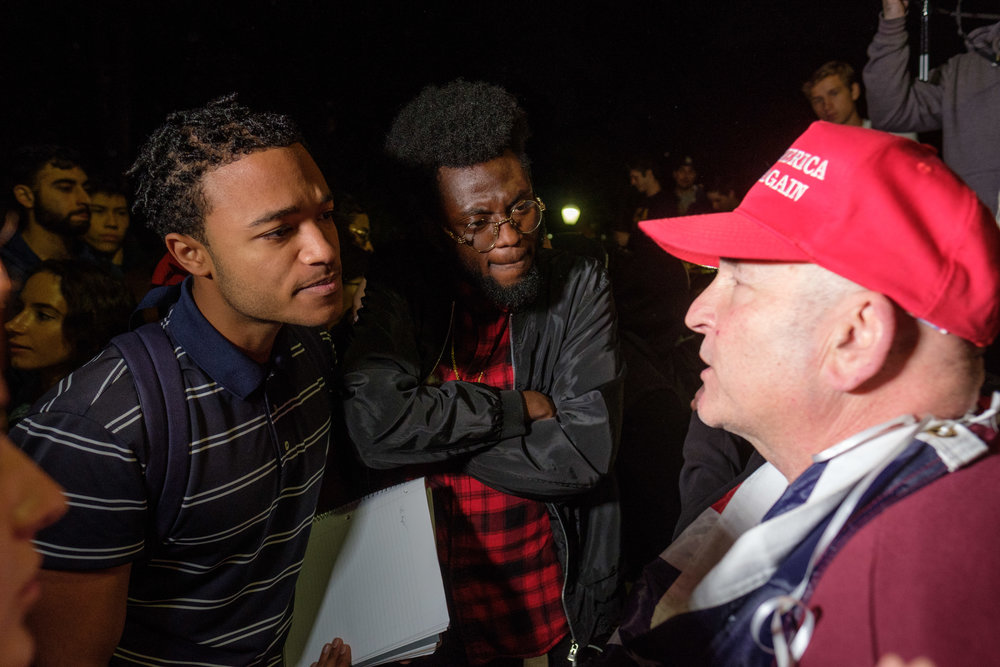 Derrick Rose a UCLA student and Kosi Ogbuli a member of the UCLA Academic Affairs Commision listening intently to Trump Supporter Greg Susca about his beliefs during the Rally Against Hate out of the Ackerman Union building in Los Angeles, CALIF on November 13, 2017. (Photo by Jayrol San Jose)