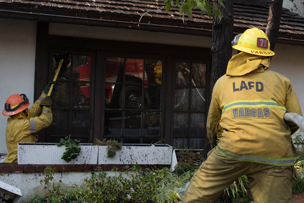 Luis Vargas (right) prepares to fire his hose as David Valadez (left) breaks down a window of one of the burning houses in the Skirball Fire. The fire burned 450 acres and shut down the 405 freeway on Dec.6, 2017 in West Los Angeles Calif. (Photo by Zane Meyer-Thornton)