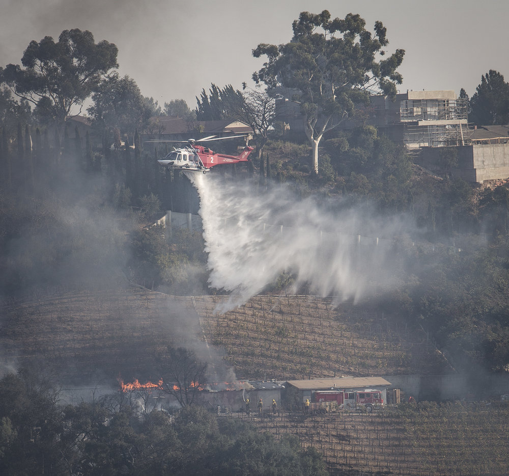 A Los Angeles Fire Department helicopter drops water to put out a burning building. The Skirball Fire shut down the 405 north and burned 450 acres of land on Dec. 6, 2017 in West Los Angeles, Calif. (Photo By: Daniel Bowyer)