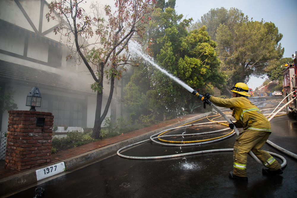 Luis Vargas, Los Angeles Fire Department, Class 1, Station 71, splashes the water to the house caught on fire on Wednesday, Dec. 6, 2017 at Casiano Boad in Bel Air, Los Angeles in California. (Photo by Yuki Iwamura)