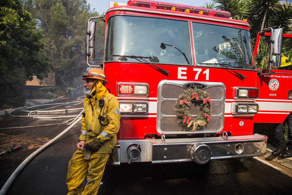 David Valadez, Los Angeles Fire Department, Class 1, Station 71 lean against their fire trucks. Firefighters arrived there at 4am, and they fights for straight over 10 hours. On Wednesday, Dec. 6, 2017. (Photo by Yuki Iwamura)