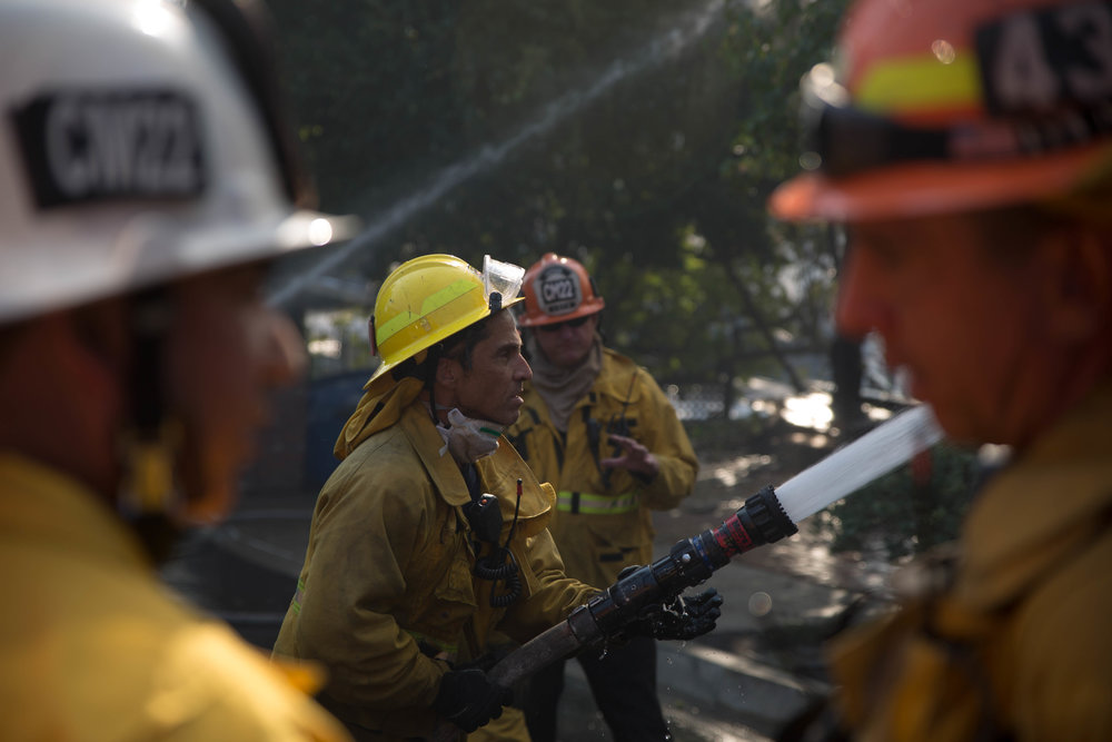 Los Angeles City firefighter Luis Vargas from Engine 71 fights to save a home on fire along Casiano Road during the Skirball Fire on Wednesday, Dec.6, 2017 in the Bel-Air area of Los Angeles, California. (Jose Lopez)